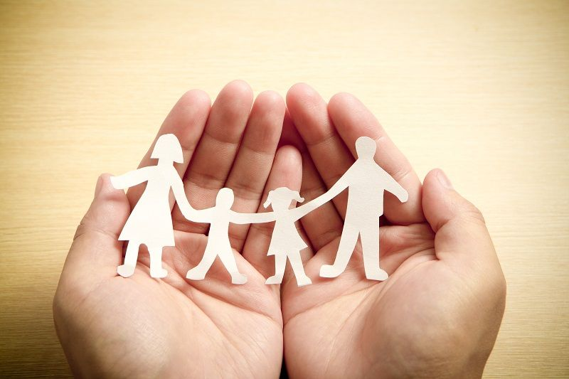 Paper-family-in-hands-with-wooden-texture-background--cm