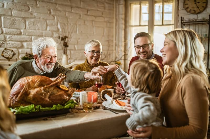Happy extended family on Thanksgiving meal at dining table-cm