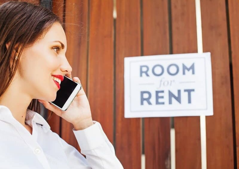 woman calling in front of Room for rent sign-cm
